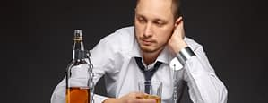 man chained to bottle of alcohol