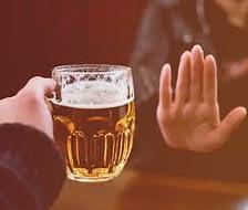rejecting a mug of alcohol