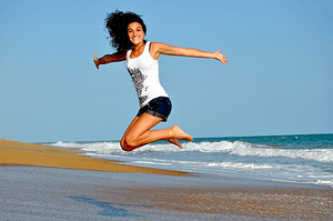 a woman jumping on the beach